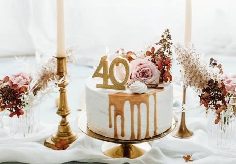 Zum runden Geburtstag erstrahlt der Geburtstagskuchen mit goldener 40 als Kerze